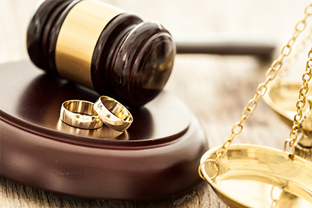 image of gavel and sound block with 2 wedding rings on it, and a golden scales of justice next to it